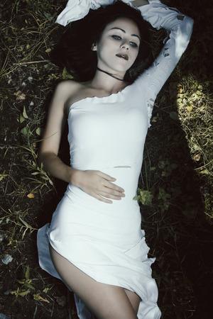 Donna pallida in vestito bianco sulla scena oscuro mistero terra