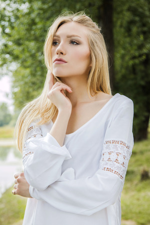 self confident: Girl in white dress outdoor looking smart and self confident Stock Photo