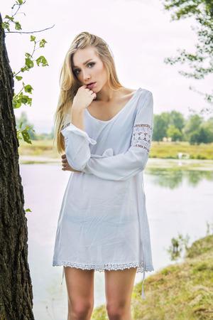 emotive: Beautiful blonde girl in white dress outdoor emotive portrait Stock Photo
