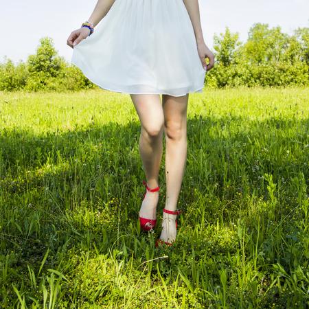 woman in field: Girl in white dress walking in the field of grass