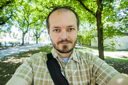 Bearded and mustache man with plaid shirt taking selfie in city