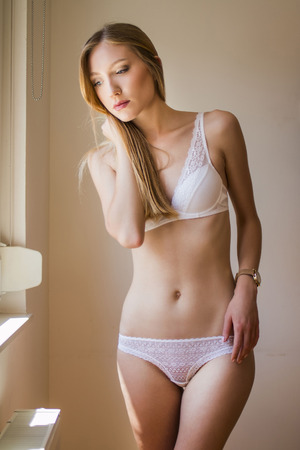 white panties: Sexy girl in white lace underwear standing next to window sunlight Stock Photo