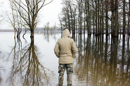 observing: Man in jacket and military pants standing on shore and observing river