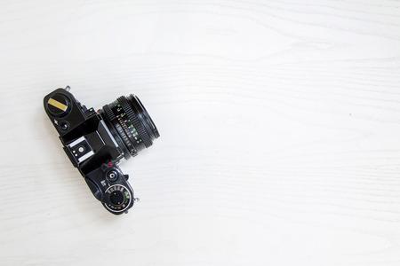 Antigua cámara analógica de 35 mm en el escritorio blanco, aislado