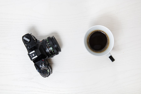 old desk: Cup of coffee and old analog camera on white desk