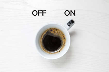 break up: Cup of coffee on white desk, switched on, concept