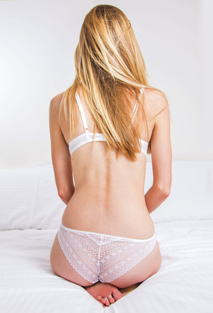 blonde long hair woman in white lace panties sitting on the bed Stock Photo