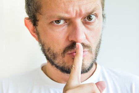 shh: Bearded man making silence gesture, pst, shh, mean expression Stock Photo