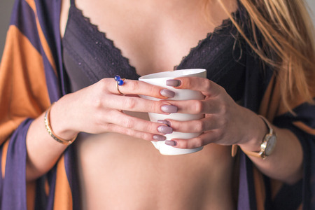 Young woman in underwear holding cup of coffee next to window in the morning, body detail