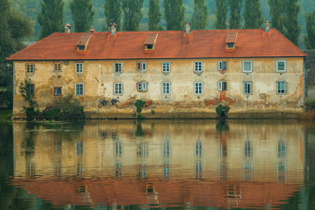 water scape: Old ruined rusty castle on the Mreznica river in Duga Resa, Croatia, reflection on water