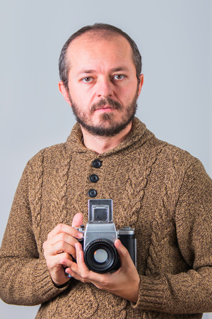 analogue: Man with beard in sweater holding old analogue medium format camera