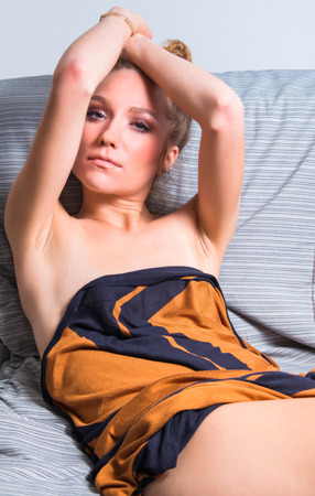 junge nackte m�dchen: Young beautiful girl lying on couch and stretching arms, eyes closed, covered with negligee, glamour beauty concept Lizenzfreie Bilder