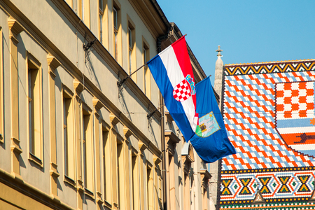 flag croatia: Flags of the Republic of Croatia and City of Zagreb on historic buildings on St Marks Square in Zagreb, Croatia, roof of St Marks church in background Foto de archivo