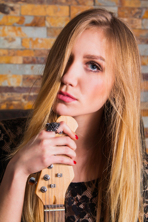 bass guitar women: Close up portrait of beautiful young girl in black lace shirt sitting and holding guitar on brick background