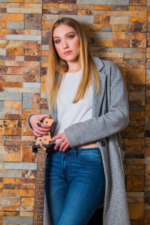 overcoat: Beautiful young girl in overcoat and jeans posing with guitar on brick background