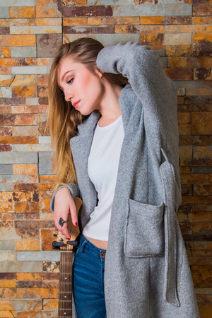 bass guitar women: Beautiful young girl in overcoat and jeans posing with guitar on brick background