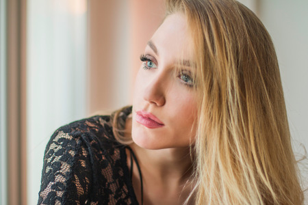 emotive: Close up portrait of beautiful young blonde woman in black lace shirt sitting next to window, looking emotive and thoughtful Stock Photo