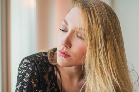 Close up portrait of beautiful young blonde woman in black lace shirt, eyes closed, sitting next to window, looking emotive and thoughtful