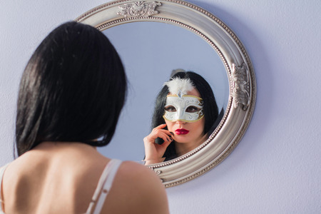Portrait of beautiful mysterious young woman in carnival mask in front of the mirror, beauty fashion concept