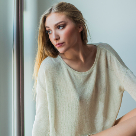 emotive: Young blonde woman sitting next to window in sweater, looking emotive and thoughtful