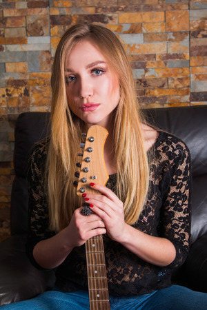 sexy young woman: Attractive young girl in black lace shirt sitting in chair and playing guitar on brick background