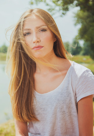warm shirt: Beautiful young blonde girl in white shirt, outdoor on lake shore, thoughtful, warm filter applied, wind in hair