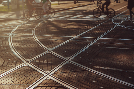 bicyclists: Tram lines intersection on the paved street in Zagreb, Croatia, intentionally blurred background with people going from work, bicyclists, commuters