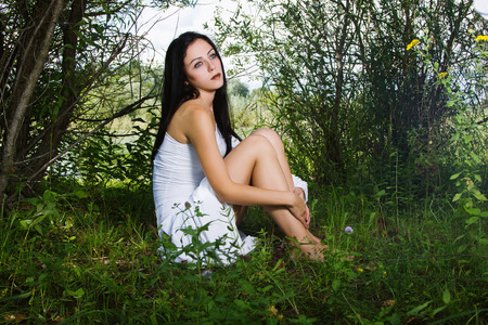 sitting on the ground: Young beautiful woman in white dress sitting on the ground, fairytale scene