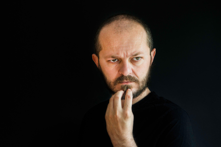 holding in arm: Serious man with beard and mustaches on black background in low key, holding arm on chin, thoughtful Stock Photo