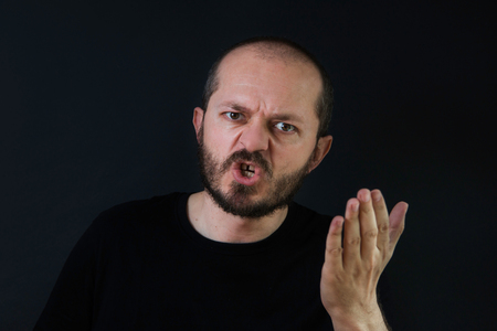 threatening: Violent, aggressive man with beard and mustaches on black background in low key, yelling and threatening Stock Photo