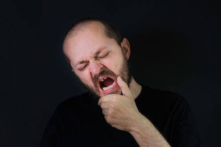 Man with beard and mustaches on black background in low key, open mouth, yawning, tired and sleepy