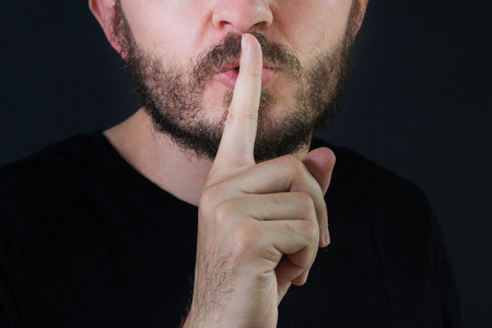 shh: Serious man with beard and mustache making silence gesture, pst, shh, face detail