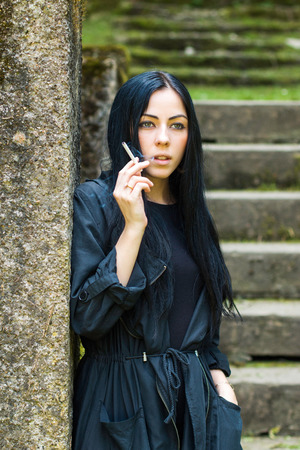 black girl smoking: Beautiful girl in black coat and dress standing next to wall on old stairs in the city, grass and trees in background, smoking a cigarette