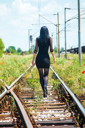nylons: Young beautiful girl in black dress and nylons walking down rail tracks, from back, cargo wagons and poppies in background