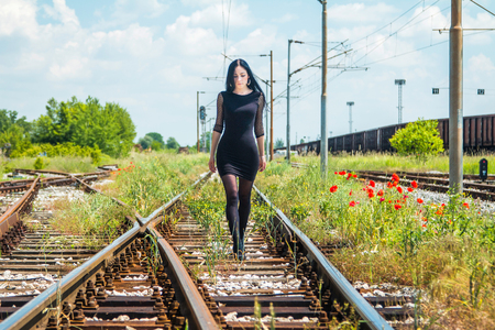 nylons: Young beautiful girl in black dress and nylons walking down rail tracks, cargo wagons and poppies in background