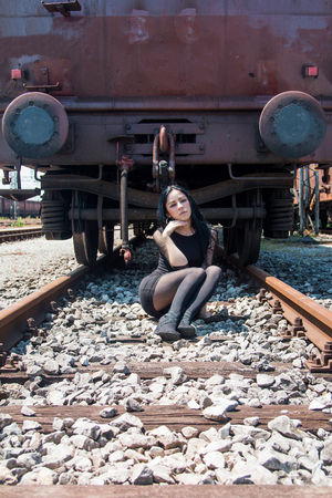 nylons: Young beautiful girl in black dress and nylons sitting on rail tracks, cargo wagons in background
