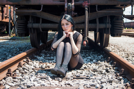 emotive: Young beautiful girl in black dress and nylons sitting on rail tracks, cargo wagons in background, emotive portrait Stock Photo