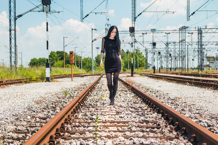 nylons: Young beautiful girl in black dress and nylons walking down rail tracks, cargo wagons in background