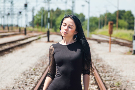 nylons: Half length of a young pretty girl in black dress and nylons walking down rail tracks, cargo wagons in background, eyes closed Stock Photo