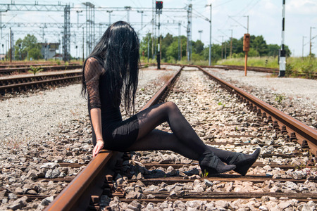 nylons: Young beautiful girl in black dress and nylons sitting on rail tracks, cargo wagons in background, face covered with hair, anonymous
