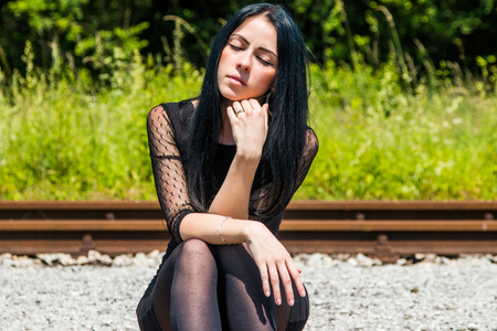 nylons: Young beautiful girl in black dress and nylons sitting on rail tracks and daydreaming, eyes closed, green grass and trees in background