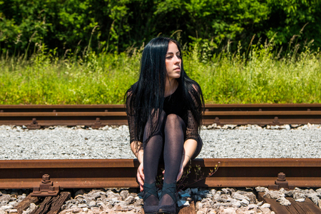 nylons: Young beautiful girl in black dress and nylons sitting on rail tracks and daydreaming, green grass and trees in background Stock Photo