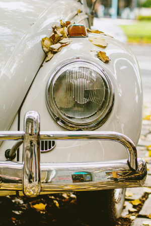 Old car parked on the street, front light detail, selective focus