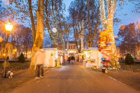 advent time: Advent time in the center of Zagreb, Croatia, people gathering in Zrinjevac park with food stands, blurred motion, unrecognizable people