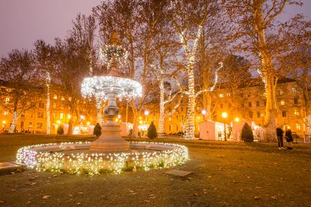 croatian: Illuminated fountain in Zrinjevac park, Zagreb, Croatia, Christmas market, Advent