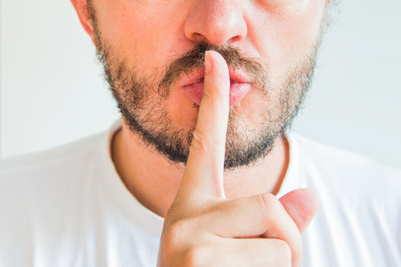 Brodaty mężczyzna czyniąc gest ciszy, PST, cii, fragment twarzy