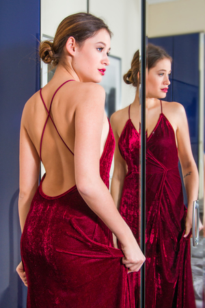 Portrait of beautiful young woman in red dress with naked back, standing in front of the mirror, beauty fashion concept, blurred background