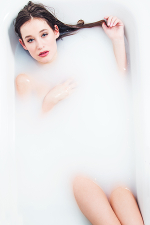 Young nude girl lying and relaxing in bathtube with milk, body detail, sexy erotic concept, joy, rejuvenation, treatment