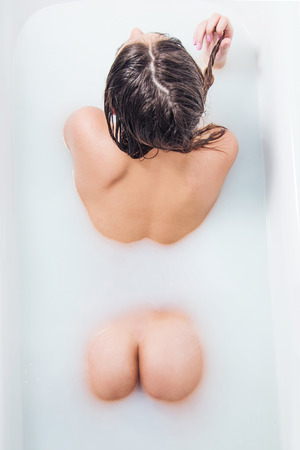 Young girl enjoying in bathtub with milk, sexy erotic concept, anonymous, view from above