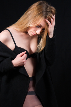 Sexy lady with glamour makeup and long blonde hair in underwear and long coat posing in studio, dark background. Elegant woman wearing black sensual lingerie. Erotic noir concept.